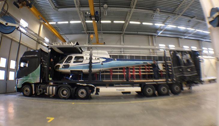 tunga lyft lastbil med helikopter på flaket